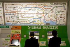 Tokyo JR line ticket fare. People buying tickets on the automatic ticket machine under the JR railway route price list in Japanese, Tokyo Station, Japan Royalty Free Stock Photos