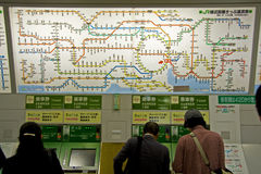 Tokyo JR railway route price list. People buying tickets on the automatic ticket machine under the JR railway route price list in Japanese, Tokyo Station, Japan stock photo