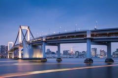 Tokyo-Regenbogen-Brücke und Tokyo ragen am Abend hoch Stockbild