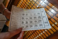 Tokyo shrine fortune paper japanese. Tokyo shrine fortune paper write japanese in woman hands japan royalty free stock photos