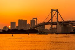 Tokyo skyline and rainbow bridge at sunset in Odaiba waterfront. royalty free stock image