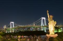 Tokyo-Stadtbild mit Regenbogenbrücke und Freiheitsstatuen lizenzfreie stockfotografie