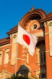 Tokyo Station with Japan National Flag. Tokyo Station old brick facade with Japan Nation Flag waving in front of it stock photo