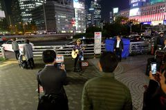 Tokyo :Street performer. Crowd watching performer in the streets outside Shinjuku station, Tokyo Japan royalty free stock images