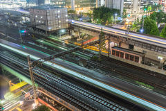 Tokyo trains and traffic at night. Local train and Shinkansen with car and foot traffic underneath Royalty Free Stock Photos