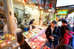 Tokyo: Tsukiji Seafood Fish Market. Workers selling fresh seafood at the Tsukiji Wholesale Seafood and Fish Market in Tokyo Japan. Locals and tourist visit the royalty free stock image