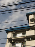 Tokyo Wires. Tokyo is notorious for its huge amount of wires hanging freely everywhere. This photo shows them in front of a typical Japanese housing complex royalty free stock image
