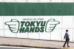 Tokyu Hands sign. TOKYO, JAPAN - 21 JUNE 2016: A direction sign for the iconic Tokyu Hands store  points to a passerby, in Shibuya, Tokyo Royalty Free Stock Image