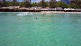 Toldos de la playa de las palmas y de las personas que practica surf en olas oceánicas metrajes