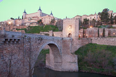 Toledo - Alcazar und Brücke Punte de Alcantara Stockfotografie