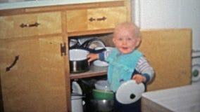 TOLEDO, OHIO 1968 : Garçon d'enfant en bas âge jouant avec des pots dans des buffets banque de vidéos
