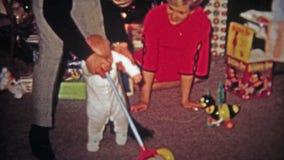 TOLEDO, OHIO 1968 : Les premières étapes de bébé aident du jouet de fauchage de père de mère banque de vidéos