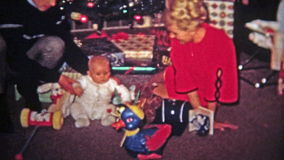 TOLEDO, OHIO 1968: Mom dad baby play new Christmas gift toy