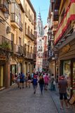 Tourists on a narrow street on the medieval city of Toledo in Spain. TOLEDO,SPAIN - AUGUST 8,2017 : Tourists on a narrow street on the medieval city of Toledo in Royalty Free Stock Images