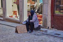 Toledo, Spanje; 23 december 2 017: Een droevige niet geïdentificeerde dakloze vrouwenzitting in een kartondoos die het bedelen vo Stock Afbeeldingen