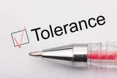 Tolerance - checkbox with a cross on white paper with pen. Checklist concept stock images