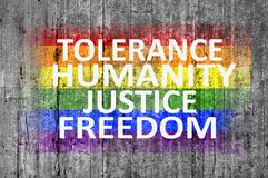 Tolerance, Humanity, Justice, Freedom and LGBT flag painted on concrete texture Stock Photo