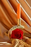 Tolerance, symbol. Red rose next to a candle, in a beautiful golden background, suggesting tolerance and prayer Stock Photo