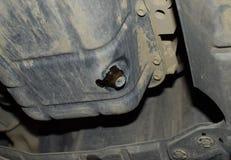 Tolga il vecchio olio dal motore tramite il tappo di scarico fotografia stock