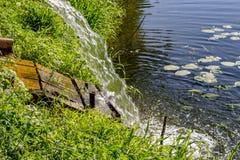 Tolga l'acqua dal tubo nel fiume immagini stock