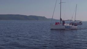 TOLIATTI RYSSLAND Circa Juli 2017 Den vita yachten seglar i vatten av floden med folk på den som vinkar händer lager videofilmer