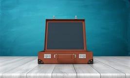 tolkning 3d av en enkel retro brun resväska med dess öppna anseende för lock på ett träskrivbord Royaltyfria Bilder