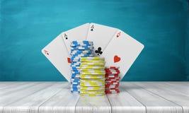 tolkning 3d av tre buntar av kasinochiper med fyra topp- kort bak dem ställning på en trätabell på en blått Arkivbild