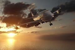 tolkning 3d från en främre sikt av en stor trafikflygplan i en solnedgång över havet Arkivfoton