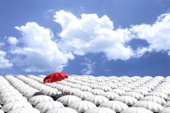 tolkning 3D: illustration av det röda paraplyet som över svävar från folkmassan av många vita paraplyer mot blå himmel och moln Royaltyfria Bilder