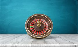 tolkningen 3d av en kasinoroulett står på dess sida på ett träskrivbord framme av en blå bakgrund Fotografering för Bildbyråer