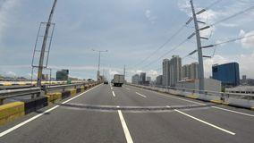Vehicle shot cruising along elevated sky highway. Toll skyway, Manila, Philippines - July 11,2017: Vehicle shot cruising along elevated sky highway overtaking stock video