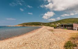 Empty beach and bar at Tollare in Corsica. Tollare, Corsica - 10th July 2018. Chez Marlene bar and retaurant on a deserted pebble beach at Tollare at the royalty free stock photography