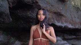 Tolles dünnes orientalisches Modell im braunen Badeanzug unter schwarzem Felsen, Haltungen für die Kamera stock video