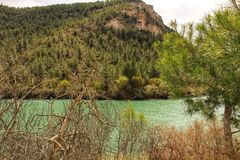 Tolosa reservoir surrounded by vegetation and mountains. In Alcala del Jucar village, Albacete, Spain Royalty Free Stock Photo