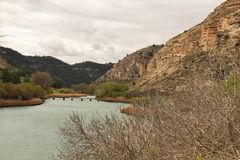 Tolosa reservoir surrounded by vegetation and mountains. In Alcala del Jucar village, Albacete, Spain Royalty Free Stock Photography