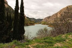 Tolosa reservoir surrounded by vegetation and mountains. In Alcala del Jucar village, Albacete, Spain Stock Photo