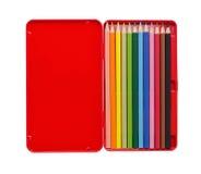Tolv färgade blyertspennor i ett rött fall med kopieringsutrymme som isoleras på vit arkivbild