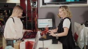 Tolyatti, ΡΩΣΙΑ - το Δεκέμβριο του 2017: Ο αγοραστής γυναικών φέρνει τα ενδύματα στην κρεμάστρα στο μετρητή με τον πωλητή στην αγ απόθεμα βίντεο