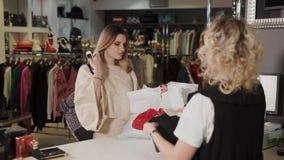 Tolyatti, RUSIA - diciembre de 2017: La mujer del vendedor es el embalar ropa pagada en un bolso en un cajero para el cliente almacen de video