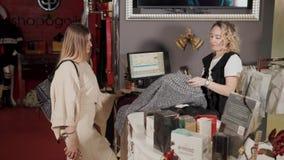Tolyatti, RUSLAND - Dec, 2017: De koper komt aan een contant geld in een klerenwinkel naderbij, tast de kassier streepjescode af stock video