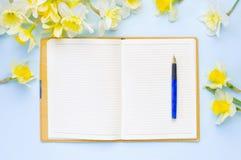 Tom öppnad anteckningsbok med gula påskliljor på ljus - blå bakgrund Lekmanna- lägenhet för bästa sikt Arkivfoto