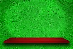 Tom överkant av röda trähyllor på bakgrund för gräsplanbusevägg, arkivfoton