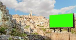 Tom affischtavla med skärmen för chromatangentgräsplan, panoramautsikt av typiska stenar Sassi di Matera och kyrka av Matera, eur lager videofilmer