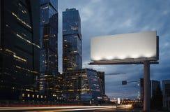 Tom affischtavla på skymning bredvid skyskrapor framförande 3d arkivfoton