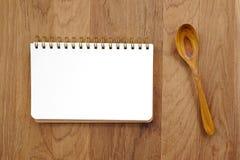 Tom anmärkningsbok och träsked på tabellen Arkivfoton