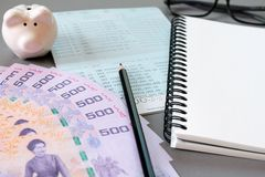 Tom anteckningsbok, blyertspenna, sparkontobankbok, ögonexponeringsglas, thailändska pengar och spargris på grå bakgrund Royaltyfri Bild