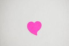 Tom anteckningsbok eller klibbiga anmärkningar som är rosa på den vita mortelväggbackgroen arkivbilder