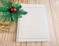 Tom anteckningsbok med chrismasbandet på wood bakgrund Royaltyfri Fotografi