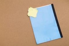 Tom anteckningsbok med fäste gula klibbiga anmärkningar Arkivfoto