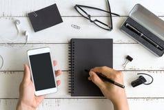 Tom anteckningsbok med mobiltelefonen på skrivbordkontor Fotografering för Bildbyråer